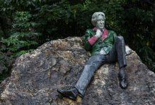 Oscar Wilde sitting on a rock.